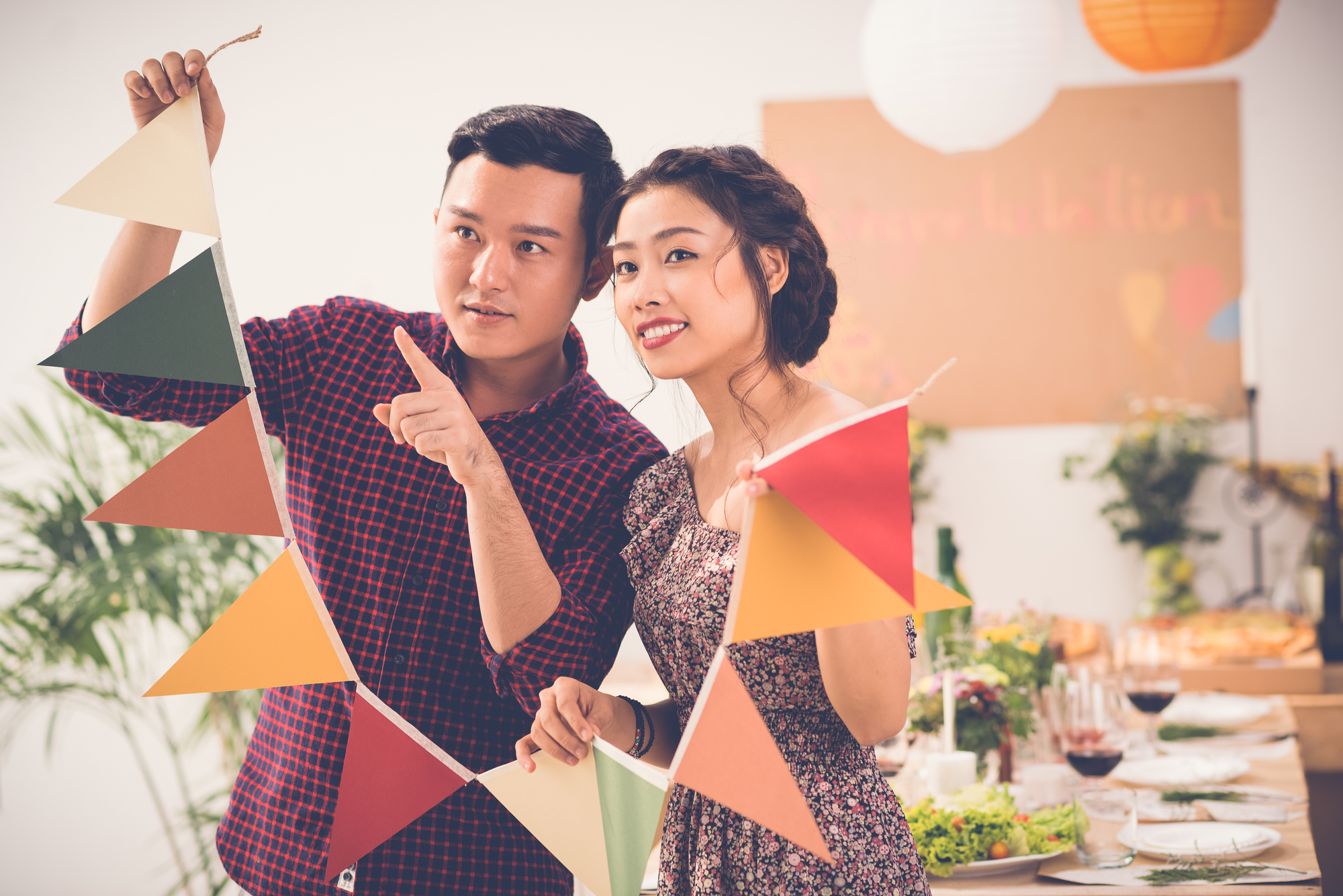Vietnamese couple deciding where to put garland when preparing for party